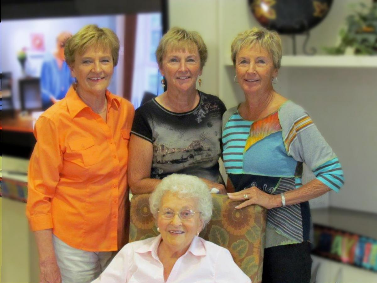 group of four women looking at the camera and smiling